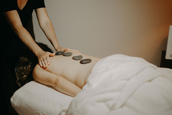 customer getting a hot stone massage at Hello Love Salon and Boutique